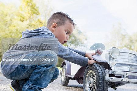 Boy checking wheel model toy vintage car