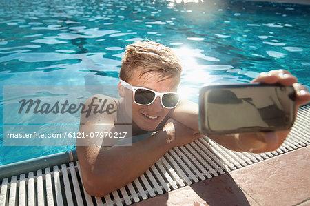 Mobile phone teenager swimming pool selfie holiday