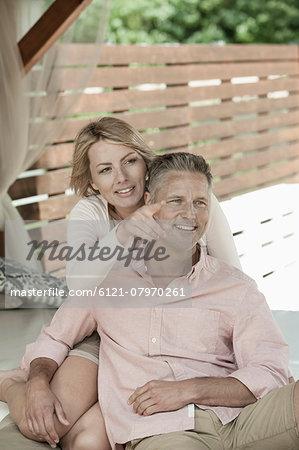 Holiday relaxing couple sitting summerhouse gazebo