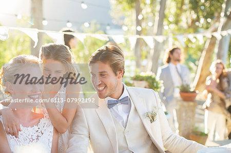 Bridesmaid whispering to bride's ear during wedding reception in domestic garden