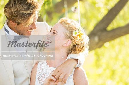 Bridegroom embracing bride in domestic garden