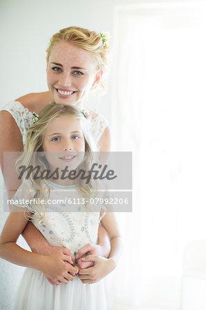 Portrait of bride and bridesmaid in domestic room