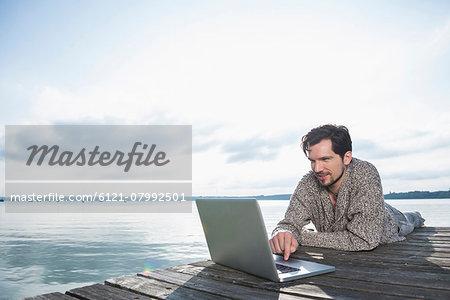 Man outdoors lake working laptop computer