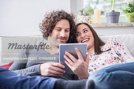 Happy couple using digital tablet, Munich, Bavaria, Germany