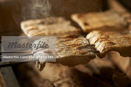 Skewered fish slices on barbeque