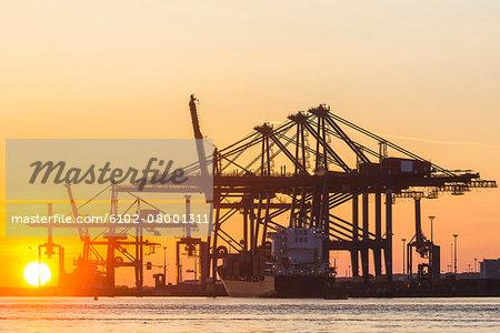 Port cranes in sunset