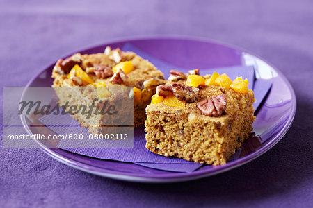 Pecan peach cake squares on a purple plate with purple napkin, studio shot on purple background