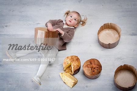 Overhead portrait of female toddler lying on floor holding pannetone cake case