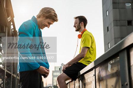 Friends taking break on bridge, Munich, Bavaria, Germany