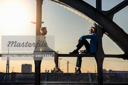 Friends relaxing on bridge, Munich, Bavaria, Germany