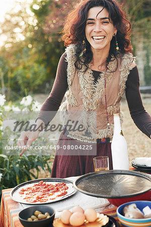 Portrait of mature hippy female preparing pizza in garden