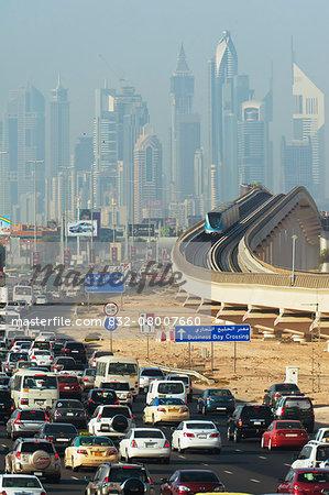 Subway Train Going Past Traffic; Sheikh Zayed Road, Dubai, United Arab Emirates