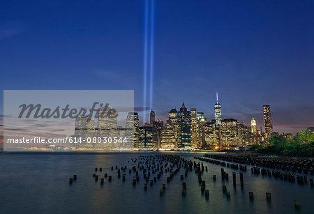 Night view of light beams over Lower Manhattan from Brooklyn Heights Promenade, New York, USA