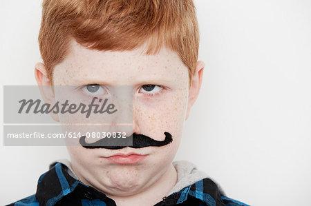 Boy wearing fake moustache, close up
