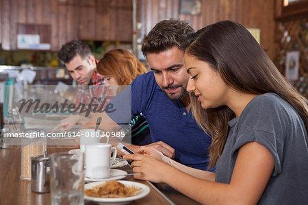 Couple looking at smartphone at restaurant bar