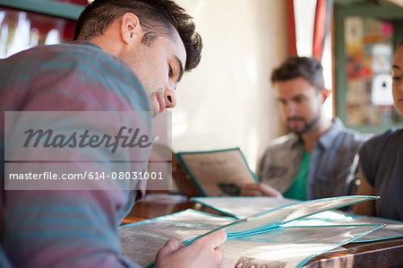 Three friends looking at menus in vegetarian restaurant