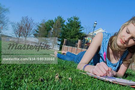 Teenage girl lying in park writing in diary