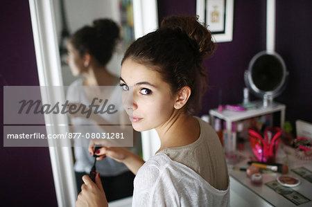 A teenage girl makeup in his room