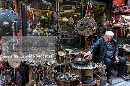 Shopkeeper with metal objects in antique shop in The Grand Bazaar (Great Bazaar) (Kapali Carsi), Beyazi, Istanbul, Turkey, Europe