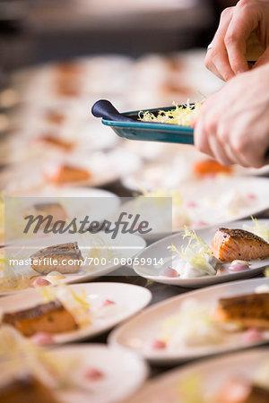 Close-up of Chef Garnishing Plates of Salmon