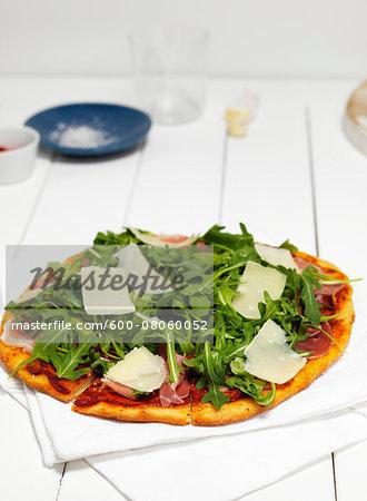 Pizza with Ham, Arugula and Parmisan Cheese on Napkin