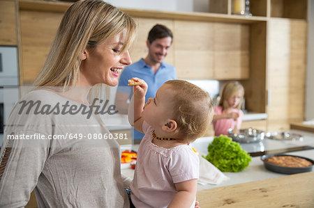 Female toddler feeding mother in kitchen