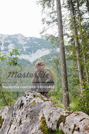 Girl sitting on rock formation in forest, Zauberwald, Bavaria, Germany