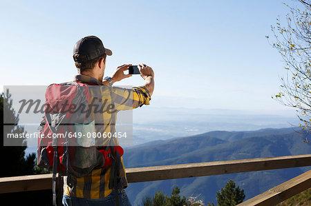 Hiker taking photograph of mountains, Montseny, Barcelona, Catalonia, Spain