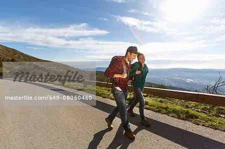 Hikers on sidewalk by hillside, Montseny, Barcelona, Catalonia, Spain