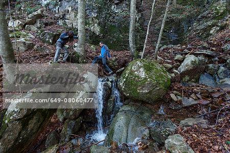 Hikers crossing stream, Montseny, Barcelona, Catalonia, Spain