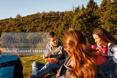 Hikers having picnic on hilltop, Montseny, Barcelona, Catalonia, Spain