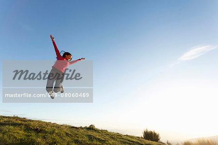 Hiker jumping on hilltop, Montseny, Barcelona, Catalonia, Spain