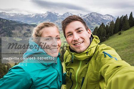 Young hiking couple taking self portrait, on the way down Zinken mountain, Oberjoch, Bavaria, Germany