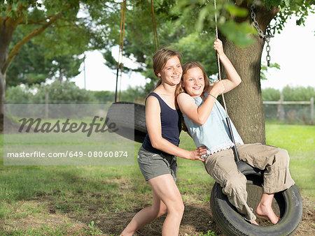 Teenage girl pushing her sister on tire swing