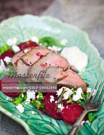 Sliced meat on beetroot salad