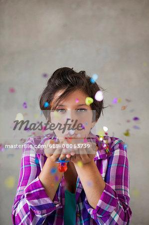 Teen girl blowing confetti