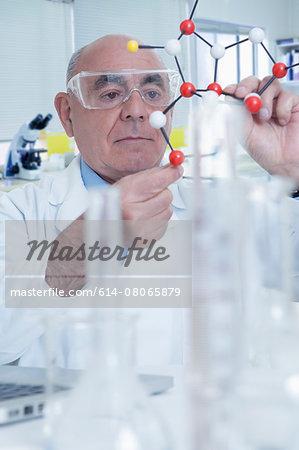 Senior male scientist holding molecular model