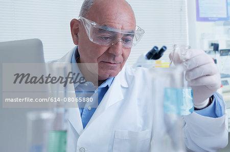 Senior male scientist looking at flask, containing blue liquid