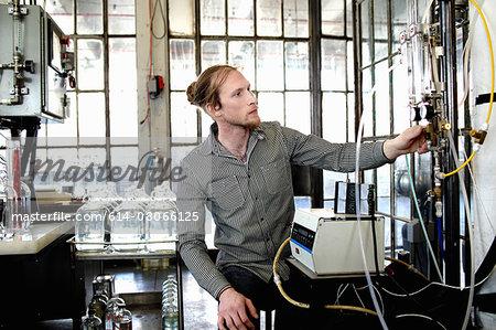 Young male vodka distiller adjusting valve in distillery workshop