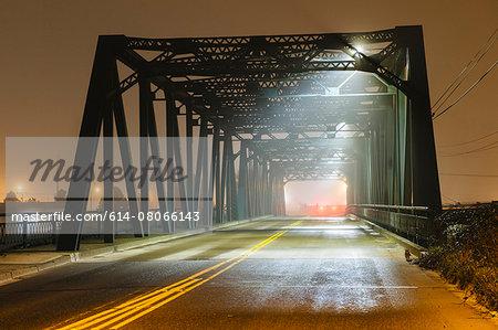 View of road and silhouetted iron bridge at night, Tacoma, Washington, USA