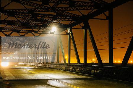 Road and silhouetted iron bridge at night, Tacoma, Washington, USA