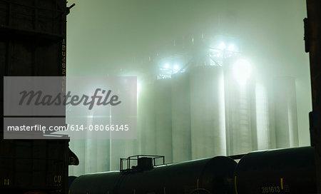 Misty view of industrial storage tanks between locomotive at night, Seattle, Washington, USA