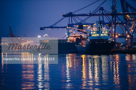 View of cargo ships and gantry cranes in harbor at night, Tacoma, Washington, USA
