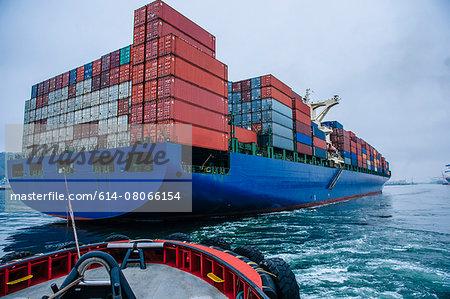 Tugboat manoeuvring container ship on river, Tacoma, Washington, USA