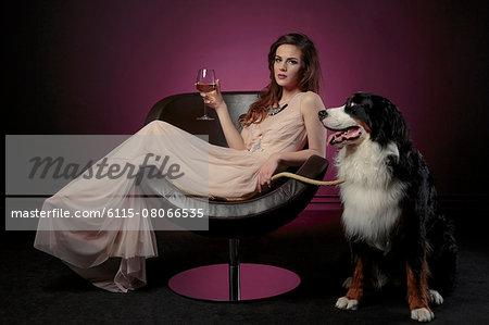 Woman drinking a glass of wine alongside huge dog