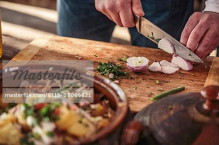 Unrecognizable person cutting onions