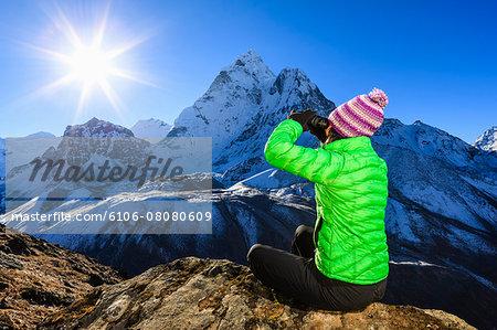 Woman looking through binoculars at Ama Dablam