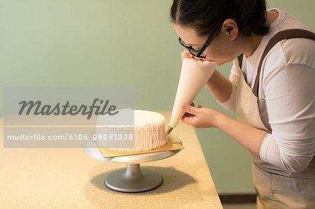 Chinese woman icing a cake