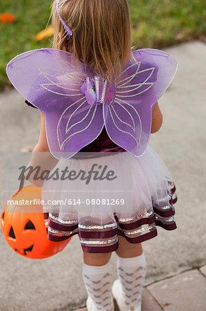 Toddler carrying Jack O' Lantern bucket