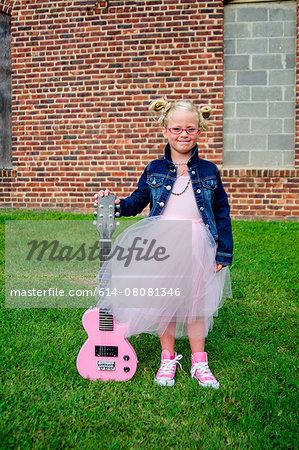 Young girl wearing tutu and denim jacket, holding guitar